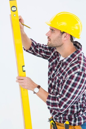 Side view of technician marking while using spirit level on white background photo