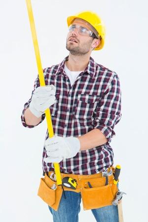 manual measuring instrument: Repairman wearing tool belt while examining spirit level on white background Stock Photo