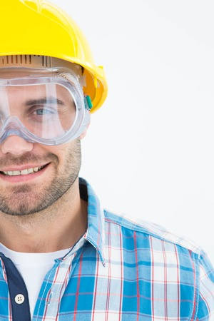 protective glasses: Portrait of confident repairman wearing protective glasses and hard hat on white background Stock Photo