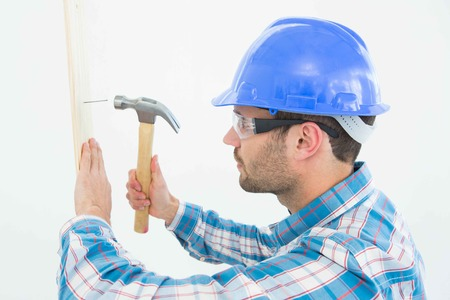 side by side: Side view of male carpenter hammering nail on wooden plank against white background Stock Photo