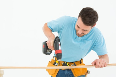 hand drill: Male construction worker using hand drill on wooden plank against white background Stock Photo