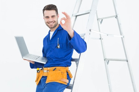 Portrait of smiling construciton worker with laptop gesturing OK while leaning on ladder against white background photo
