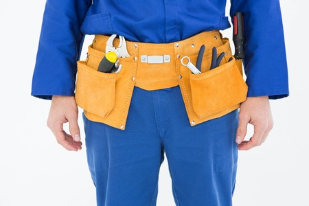 tool  belt: Cropped image of repairman wearing tool belt against white background