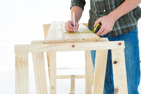 Cropped image of worker using measure tape to mark on wooden plank against white background photo
