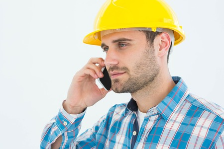 Male construction worker using mobile phone against white backgorund photo