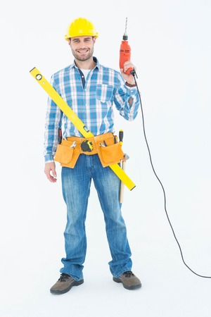 Full length portrait of smiling repairman with tools standing against white background photo