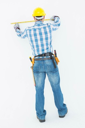 Full length rear view of construction worker using measure tape on white background photo