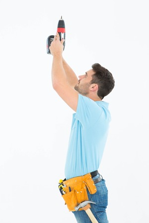 Side view of repairman using hand drill against white background photo