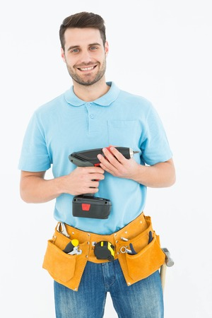 Portrait of happy repairman holding hand drill against white background photo