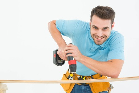 Portrait of smiling construction worker using hand drill on wooden plank against white background photo