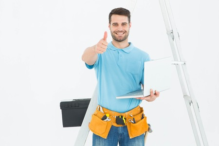 Portrait of happy construciton worker with laptop gesturing thumbs up against white background photo