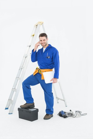Portrait of smiling repairman with toolbox and ladder using cellphone against white background photo