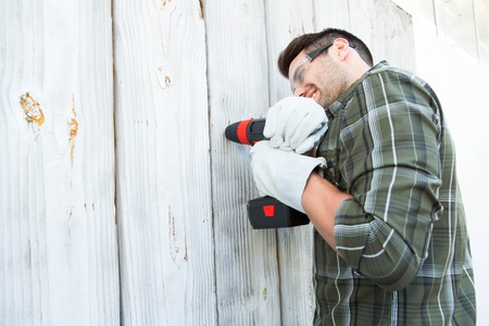hand drill: Side view of construction worker using hand drill on wooden cabin