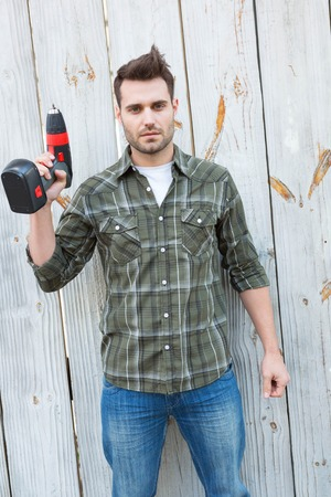 hand drill: Portrait of confident carpenter holding hand drill outside wooden cabin
