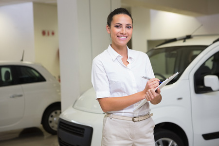 Smiling businesswoman writing on clipboard at new car showroom photo