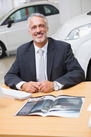selling service smile: Happy businessman working at his desk at new car showroom Stock Photo
