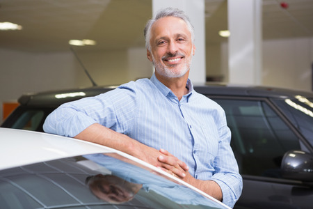 car showroom: Smiling customer leaning on car at new car showroom Stock Photo