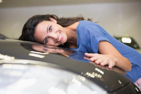 personas abrazadas: Mujer sonriente abrazando a un coche negro en la nueva exposici�n de coches