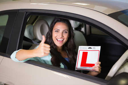 learner: Woman gesturing thumbs up holding a learner driver sign at new car showroom Stock Photo
