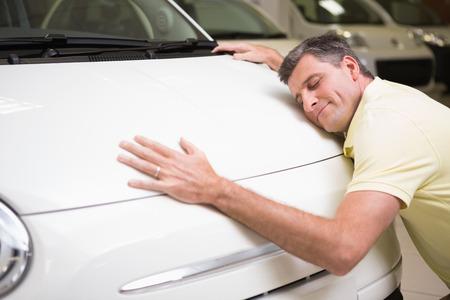 uomini maturi: Uomo sorridente abbraccia una macchina bianca a nuovo autosalone