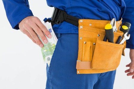 putting money in pocket: Cropped image of repairman putting euro notes in pocket against white background Stock Photo