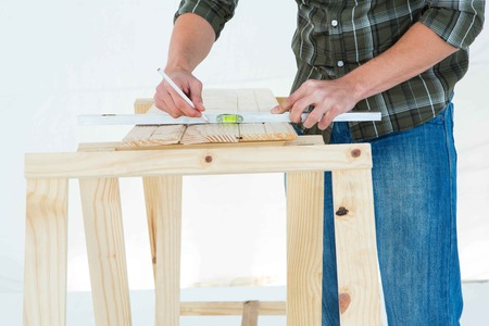 spirit level: Cropped image of worker using spirit level to mark on wooden plank against white background