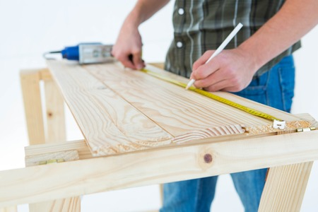Cropped image of carpenter marking with measure tape on wooden plank against white background photo