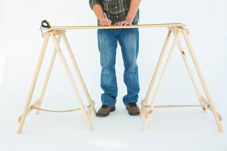 Low section of construction worker marking wooden table against white background photo