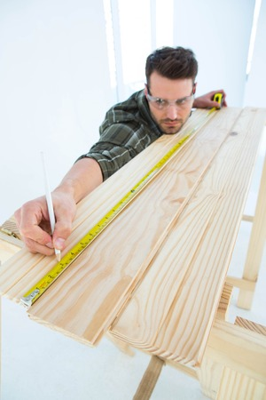 Male construction worker using measure tape to mark on wooden plank at home photo
