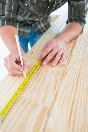 Cropped image of carpenter marking with tape measure on wooden plank against white background photo
