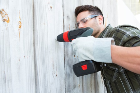 hand drill: Male carpenter using hand drill on wooden cabin Stock Photo