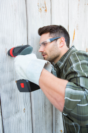 hand drill: Side view of carpenter using hand drill on wooden cabin Stock Photo