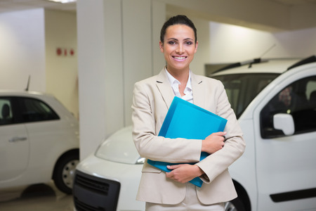 Businesswoman holding document while looking at camera at new car showroom photo