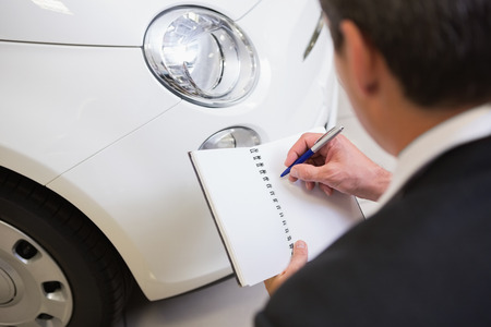 adult  body writing: Businessman looking at car while writing on clipboard at new car showroom