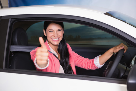 drives: Smiling woman driving while giving thumbs up at new car showroom Stock Photo