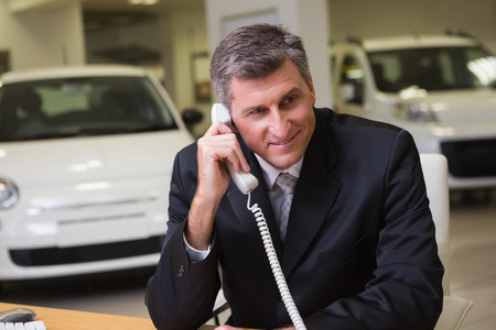 Smiling businessman using laptop on the phone at new car showroom