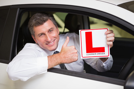 learner: Man gesturing thumbs up holding a learner driver sign at new car showroom