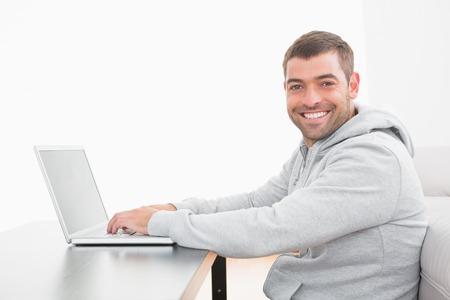 sudadera: Un hombre sonriente con una sudadera sentado en el suelo utilizando una computadora port�til