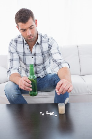 preoccupied: Preoccupied man with a beer and his medicine laid out on coffee table Stock Photo
