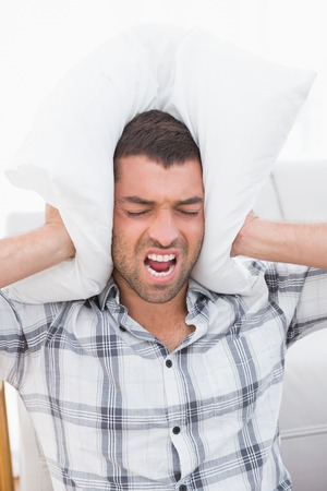 wrath: Screaming man in the living room block his hears with a pillow Stock Photo