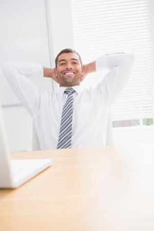 swivel chair: Businessman relaxing in a swivel chair leaning ahead