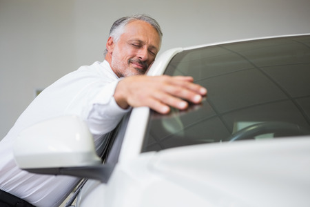 Man hugging on a car at new car showroom Stock Photo