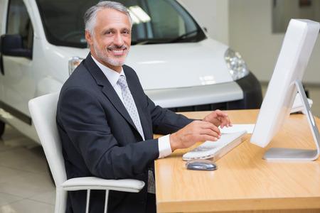 car showroom: Cheerful businessman working at his desk at new car showroom