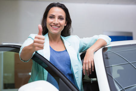 communication industry: Smiling customer leaning on car while giving thumbs up at new car showroom Stock Photo
