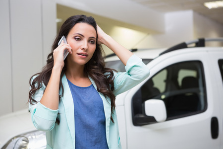 gloominess: Upset woman calling someone with her mobile phone at new car showroom Stock Photo