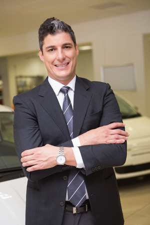 car showroom: Smiling businessman standing with arms crossed at new car showroom Stock Photo