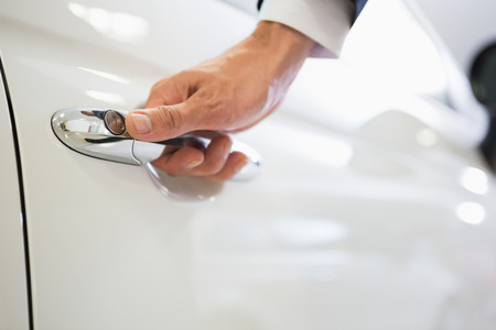car showroom: Man holding a car door handles at new car showroom Stock Photo