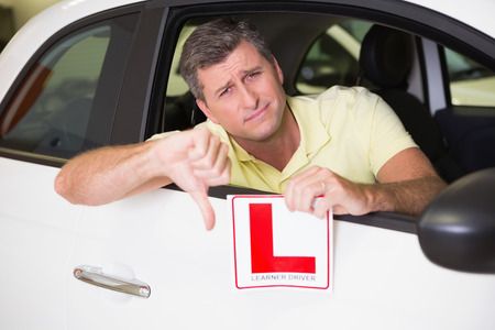 learner: Man gesturing thumbs down holding a learner driver sign at new car showroom