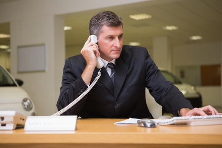 Focused businessman using laptop on the phone at new car showroom Stock Photo