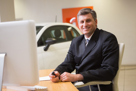 selling service smile: Smiling businessman sitting at his desk holding a car key at new car showroom